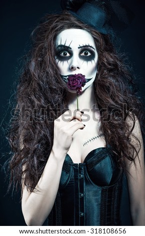 Young woman in the image of a sad gothic freak clown holds withered flower - stock photo