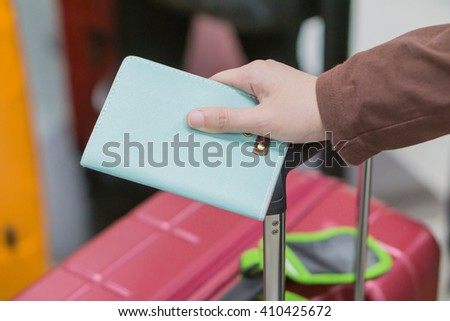 Young woman in the international airport holding passport in her hands,Tourism concept, traveler's passport.Traveling business women handing passport - airport security,selective focus,vintage color - stock photo