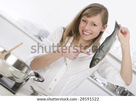 young woman in the kitchen with fish in hand - stock photo