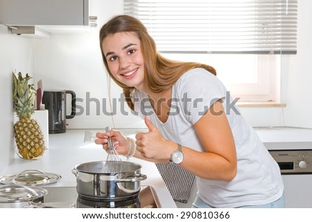 Young woman in the kitchen with thump up