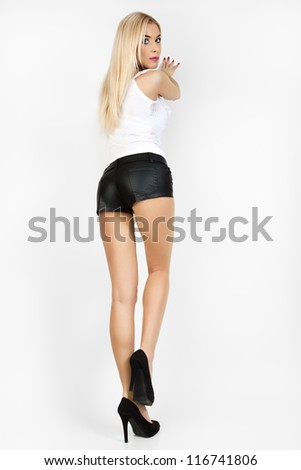 Young woman in the leather shorts. - stock photo
