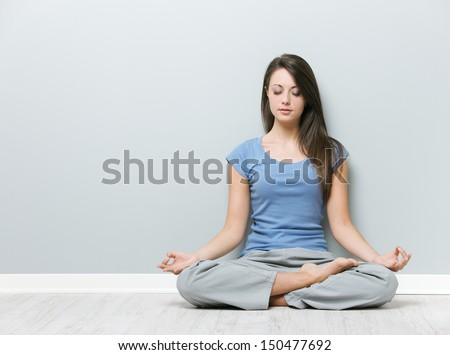 Young woman in the lotus position while meditating  - stock photo