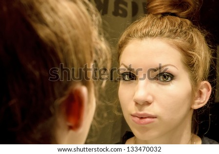 Young woman in the mirror - stock photo