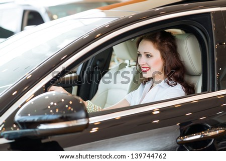 young woman in the new car in the showroom, smiling and looking in camera