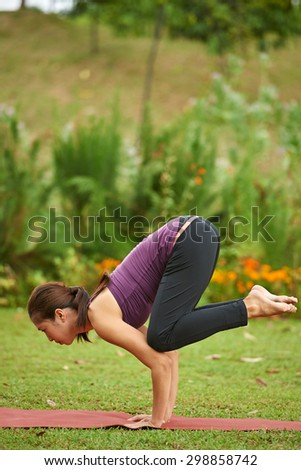 Young woman in the park doing yoga pose arm balance crow pose