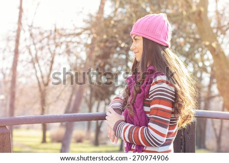 Young woman in the park looking at side. Autumn or winter season. - stock photo