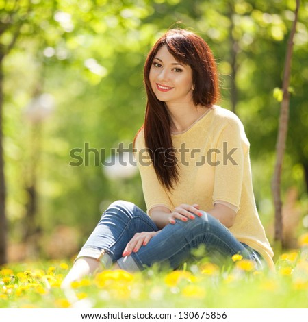 Young woman in the park with flowers - stock photo