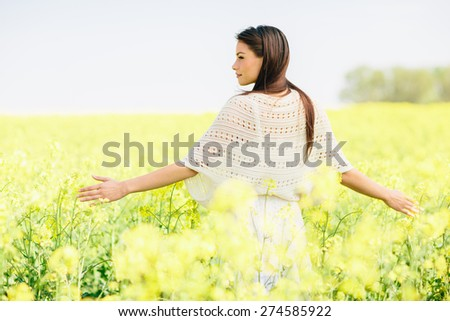 Young woman in the spring field - stock photo