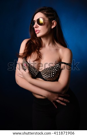 Young woman in the top with studs in front of dark background