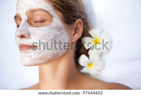 Young woman in the tropical spa making face mask - stock photo