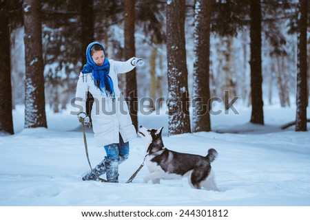 young woman in the winter park with a dog Husky - stock photo
