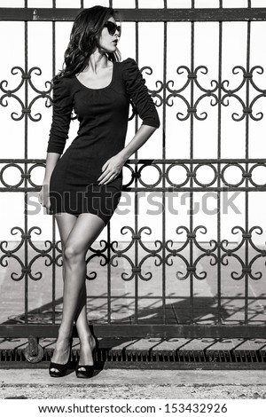 young woman in tight dress lean on wrought iron fence full body shot bw - stock photo