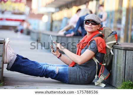Young woman in town using electronic tablet - stock photo