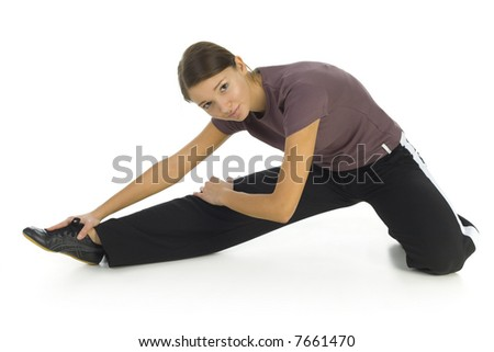 Young woman in tracksuit stretching on the floor and doing some kind of exercise. Isolated on white in studio. Side view, whole body - stock photo