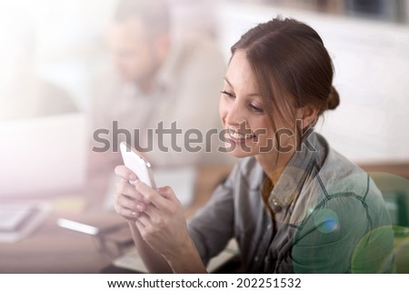 Young woman in training class sending text message - stock photo
