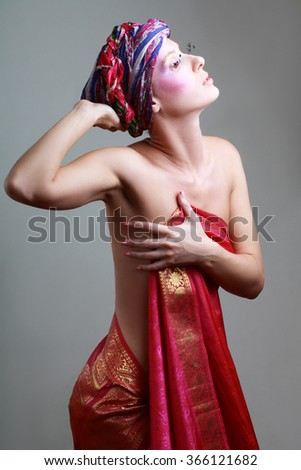 Young woman in turban and with artistic visage and false eyelashes - stock photo
