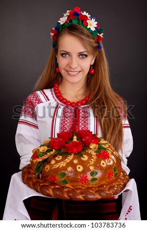 Young woman in ukrainian clothes, with garland and round loaf on black background - stock photo