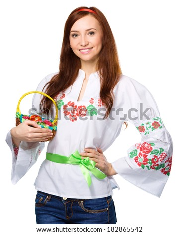Young woman in ukrainian national cloth is holding a basket full of easter eggs, isolated over white - stock photo