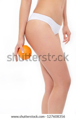 Young woman in underwear with orange showing absence of cellulite and perfect body over white background