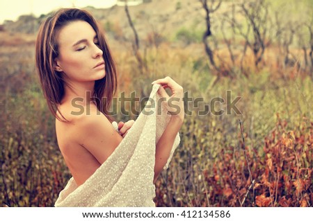 Young woman in veil standing on the field - stock photo