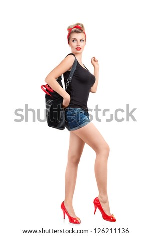 Young woman in vintage pin-up style dress posing against white background