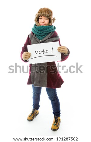 Young woman in warm clothing and showing vote sign on white background - stock photo