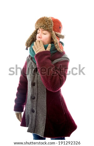 Young woman in warm clothing and yawning - stock photo