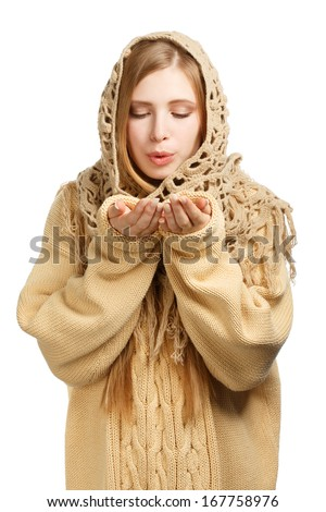 Young woman in warm comforter and knitted sweater blowind on her hands isolated on white background - stock photo