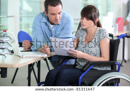 Young woman in wheelchair working with a male colleague - stock photo