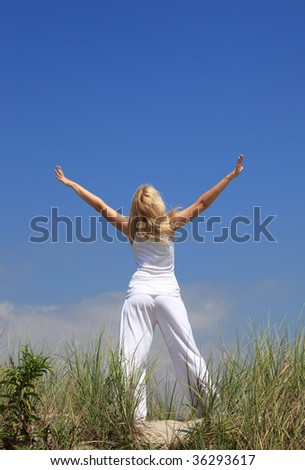 Young woman in white clothes relaxing among dunes - stock photo
