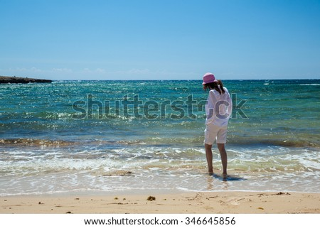 Young woman in white clothes walking along the seashore