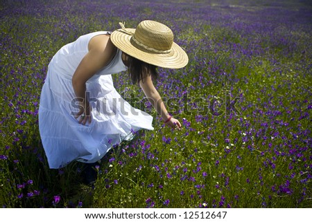 young woman in white dress and had in the middle of a flower field - stock photo