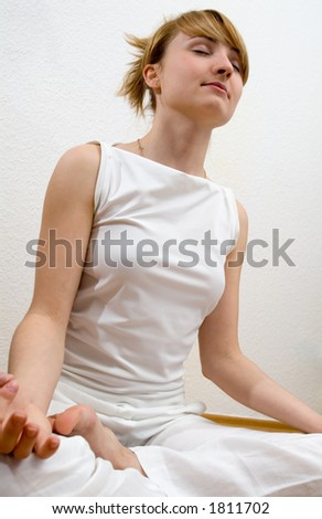 young woman in white dress doing yoga and relaxing