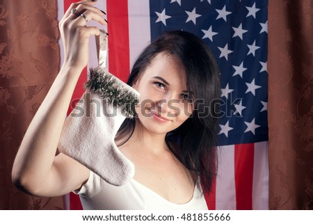 Young woman in white dress holding in hands Christmas sock ,Winter holidays, brunette on American flag background