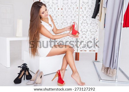 Young woman in white dress sitting in a chair in the store and choosing shoes