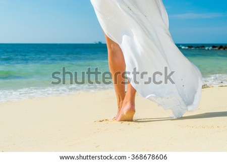 Young woman in white dress walking alone on the beach - stock photo