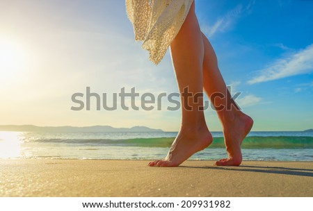 Young woman in white dress walking alone on the beach in the sunrise. Closeup detail of female feet and golden sand on beach. - stock photo
