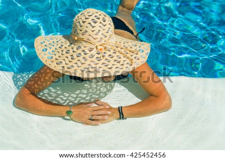 young woman in white hat resting in the swimming pool. - stock photo