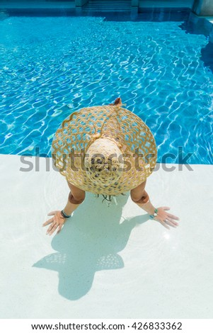 young woman in white hat resting in the swimming pool.