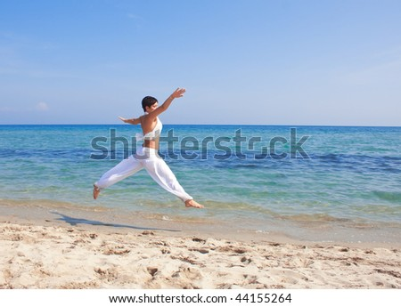 young woman in white  jumping on the beach