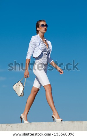 Young woman in white outdoors. Attractive woman in white walking on background of sky - stock photo