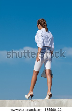 Young woman in white outdoors. Attractive woman in white walking on background of sky. Rear view - stock photo