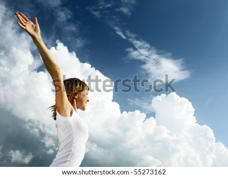 Young woman in white shirt over blue sky with fluffy clouds - stock photo