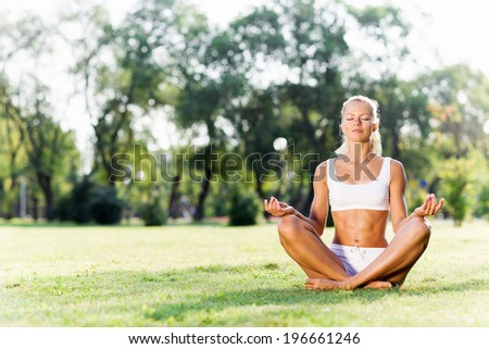Young woman in white sitting on grass in lotus pose - stock photo