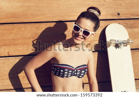 Young woman in white sunglasses sitting with a skateboard in the daytime. Outdoors, lifestyle - stock photo