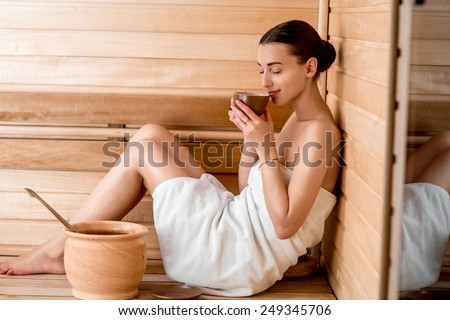 Young woman in white towel drinking tea sitting in Finnish sauna - stock photo