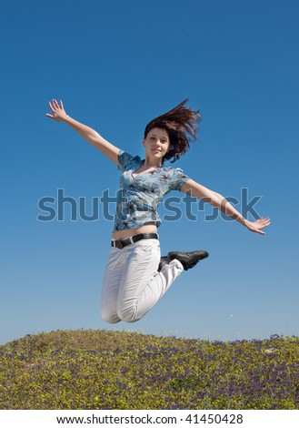 Young woman in white trousers is jumping on background of the sky