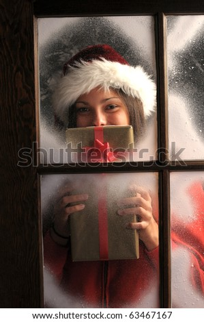 Young woman  in window covered with frost holding a Christmas Present in front of her face vertical composition.