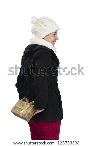 young woman in winter clothes hiding a present behind her back - stock photo