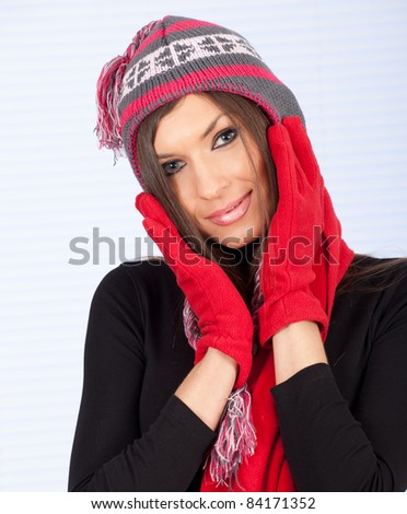 young woman in winter hat and mittens with hands near face - stock photo